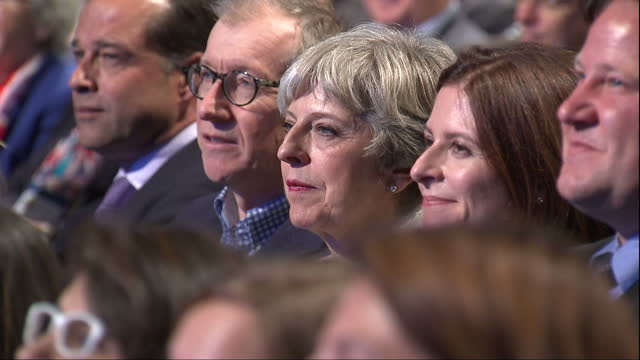 Interior shots of Prime Minister Theresa May sitting next to her husband Philip May and smiling and looking serious as she listens in the audience at...