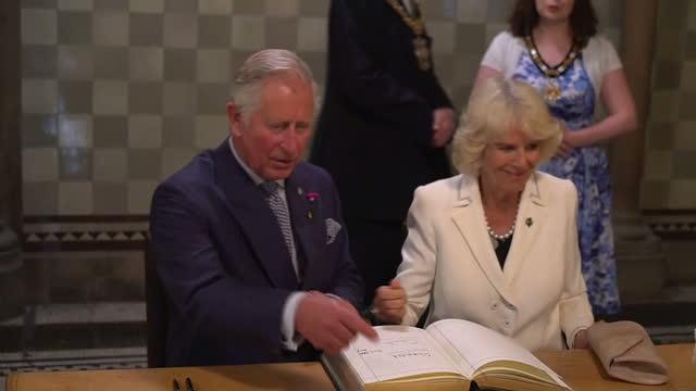 Interior shots of Prince Charles and Camilla Duchess of Cornwall signing the visitors' book and a message of condolence after attending a reception...