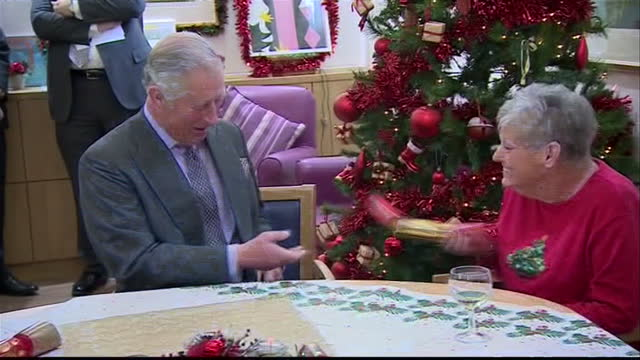 interior shots of prince charles prince of wales opening christmas crackers with people at the hospice and read one of the jokes inside it which he... - cracker stock videos and b-roll footage