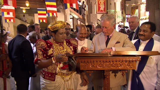 interior shots of prince charles signing the visitor's book during a visit to the temple of the tooth in kandy prince charles and duchess of cornwall... - signierstunde stock-videos und b-roll-filmmaterial