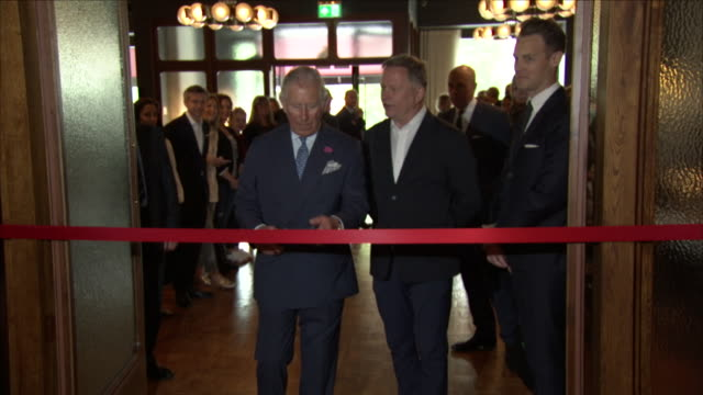 interior shots of prince charles speaking to people on his arrival including shots of prince charles cutting a red ribbon as he enters the room on... - cut video transition stock videos & royalty-free footage