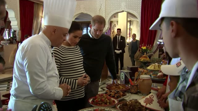 interior shots of prince harry and meghan duchess of sussex watching a cooking demonstration and trying local food before being presented with aprons... - royalty stock videos & royalty-free footage