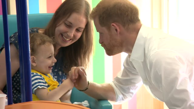 interior shots of prince harry duke of sussex plays with one year old noah nicholson during a visit to sheffield children's hospital on 25th july... - シェフィールド点の映像素材/bロール