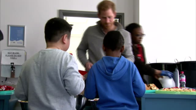 Interior shots of Prince Harry helping to serve lunch to young people taking part in a Fit and Fed February halfterm holiday activity programme at...