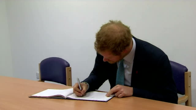 interior shots of prince harry signing the visitors book and close up shots of his signature at mildmay hospital on december 14, 2015 in london,... - レトロウィルス点の映像素材/bロール