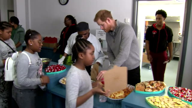 Interior shots of Prince Harry speaking to staff in the kitchen at Roundwood Youth Centre before putting on gloves and helping to serve lunch to...