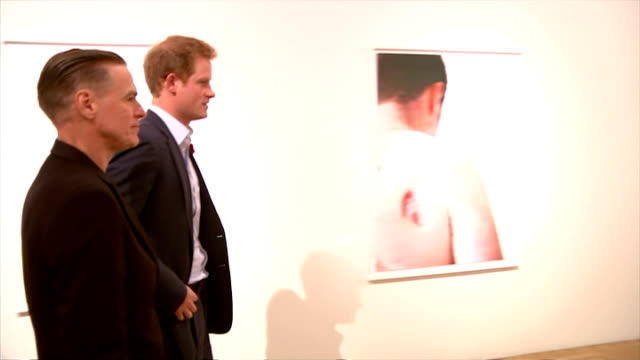 vidéos et rushes de interior shots of prince harry with singer bryan adams and itn journalist caroline frogatt inspecting pictures of wounded soldiers in gallery and... - bryan adams