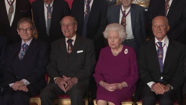 interior shots of prince philip and the queen in a photo op with guests at the order of merit lunch including a shot of prince philip and sir david... - königin elisabeth ii. von england stock-videos und b-roll-filmmaterial