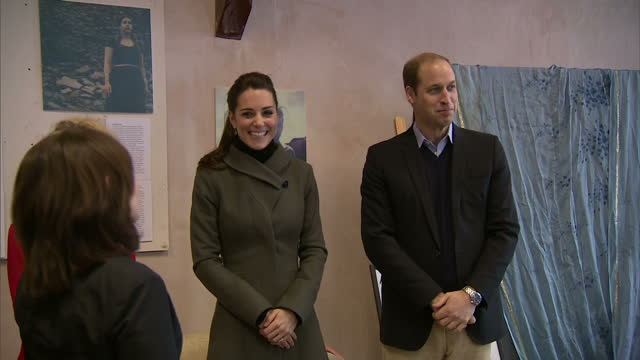 Interior shots of Prince Wiliiam and Catherine Duchess of Cambridge on a visit to the Mind charity being presented with a bunch of flowers before...