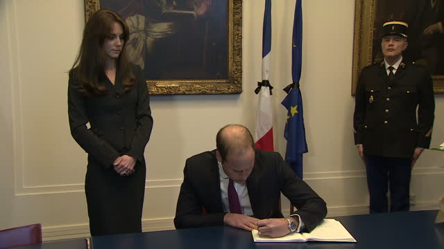 interior shots of prince william and catherine duchess of cambridge signing the book of condolence to the victims of the paris terror attacks at the... - duchess of cambridge stock videos and b-roll footage