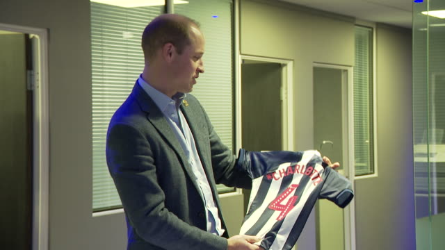 interior shots of prince william being gifted west bromwich albion t shirts for princess charlotte and prince louis with their names on the back and... - shirt stock videos & royalty-free footage