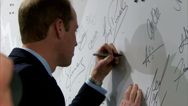 vídeos de stock, filmes e b-roll de interior shots of prince william duke of cambridge signing a wall at st george's park and close up shots of his and kelly holmes' signatures on may... - evento de autógrafos