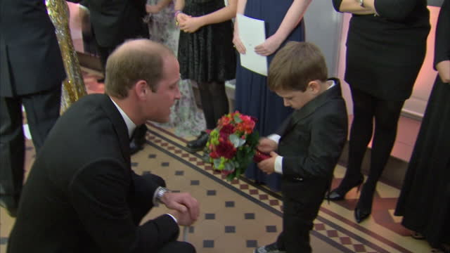Interior shots of Prince William Duke of Cambridge speaking to a shy young boy asking if the flowers are for Catherine at the Royal World Premiere of...