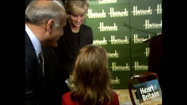 interior shots of princess diana, princess of wales, being presented with bouquet of flowers at heart of britain book launch at harrods book... - フラワーアレンジメント点の映像素材/bロール