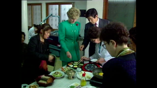 vidéos et rushes de interior shots of princess diana princess of wales walking into kitchen during school visit and trying sushi turning away from camera to eat during... - 1992