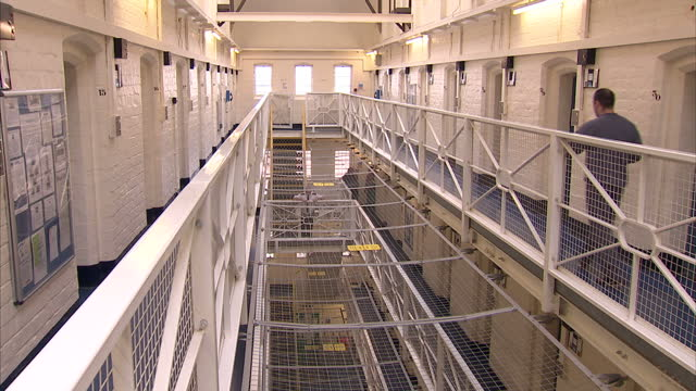 clean interior shots of prison hallway with anonymous prisoners and officers walking around and interior shots of prison cell on january 18 2012 in... - prisoner rehabilitation stock videos & royalty-free footage