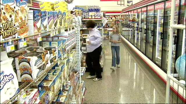 interior shots of products for sale in a us supermarket and customers browsing, including the bakery aisle and various cakes and crisps and snacks on... - unhealthy eating video stock e b–roll