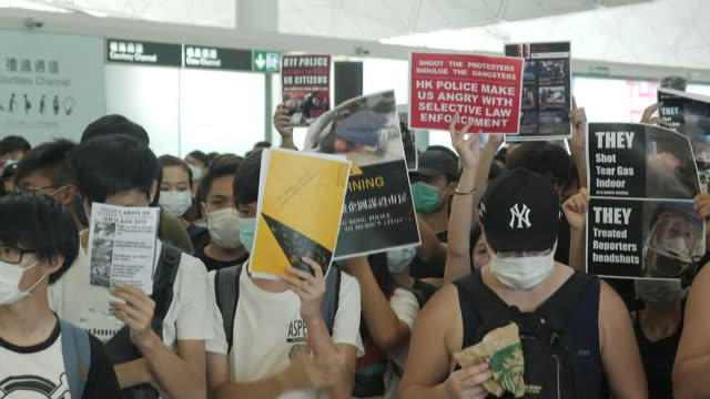 interior shots of protesters in face masks inside hong kong international airport departures hall holding protest banners and blocking entrances to... - hong kong international airport stock videos & royalty-free footage