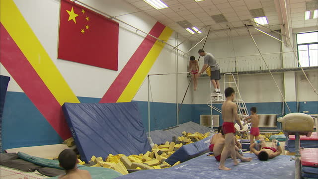 stockvideo's en b-roll-footage met interior shots of pupils being trained in gymnastics skills including boys practising on the parallel bars and high bar at a gymnasium at shichahai... - de brug