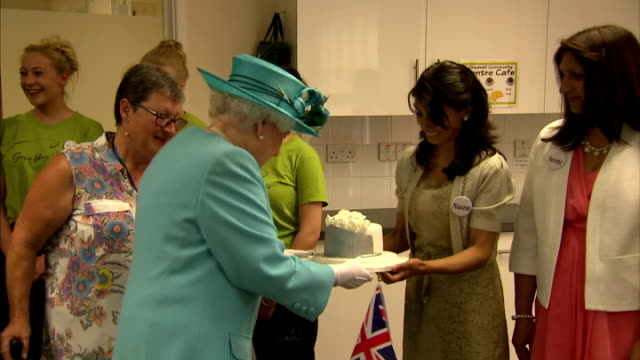 Interior shots of Queen Elizabeth being presented with a cake whilst visiting Chadwell Community Centre on July 16 2015 in Dagenham England