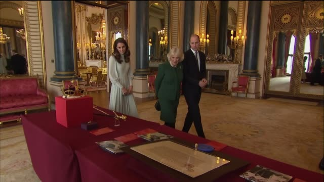 interior shots of queen elizabeth ii and prince charles wallking over to table displaying investiture regalia with camilla duchess of cornwall prince... - königin stock-videos und b-roll-filmmaterial