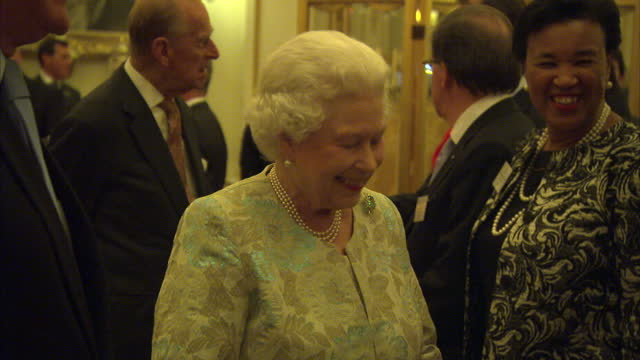 Interior shots of Queen Elizabeth II and Prince Philip greeting guests at a reception being held for members of the Jubilee Trust on the day Prince...