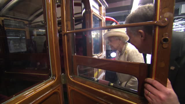 vidéos et rushes de interior shots of queen elizabeth ii and prince philip looking at old train carriage with wooden frame. royals visit baker street tube station at... - wagon