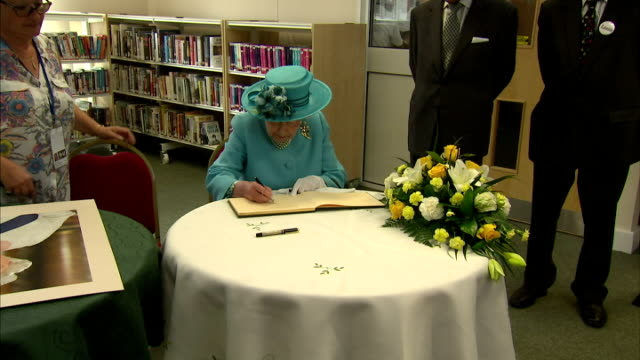 vidéos et rushes de interior shots of queen elizabeth ii and prince philip signing book and autographing poster at chadwell heath community centre on july 16 2015 in... - autographe