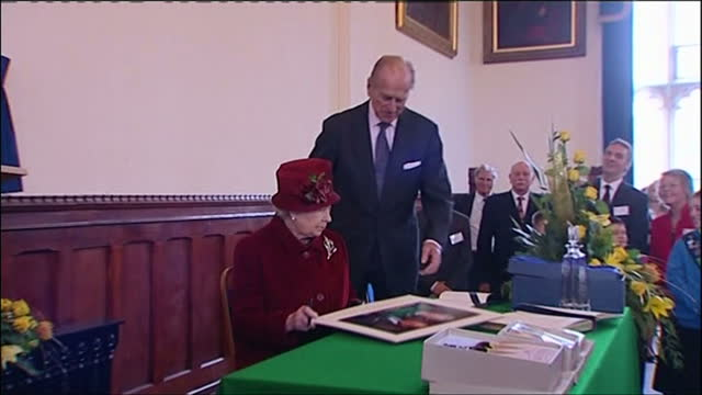 Interior shots of Queen Elizabeth II and Prince Philip unveiling a plaque and signing a guest book during a visit to Banbury town centre on November...