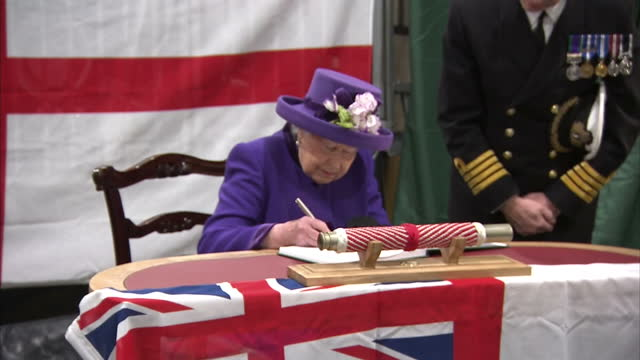 Interior shots of Queen Elizabeth II attending the Commissioning Ceremony For the Royal Navy's new aircraft carrier HMS Queen Elizabeth signing book...