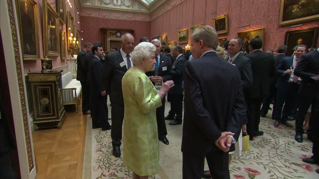 Interior shots of Queen Elizabeth II greeting guests at reception for the Awards for Enterprise at Buckingham Palace on July 14 2015 in London England