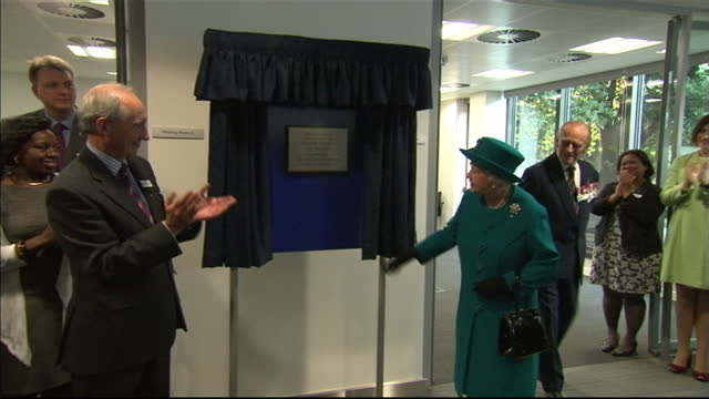 interior shots of queen elizabeth ii unveiling a plaque commemorating the official opening of the ssafa headquarters and being presented with a... - medaglia premio video stock e b–roll