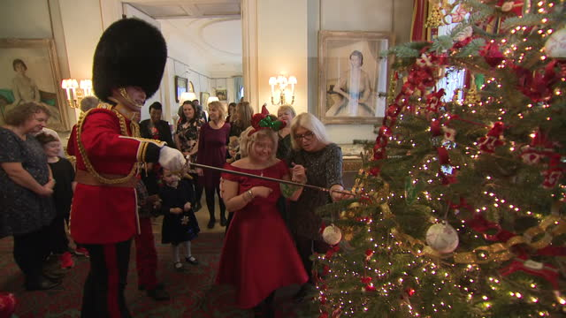 interior shots of queen's guard soldier helping children attach decorations to christmas tree with his sword inside clarence house on 13th december... - royalty stock videos & royalty-free footage
