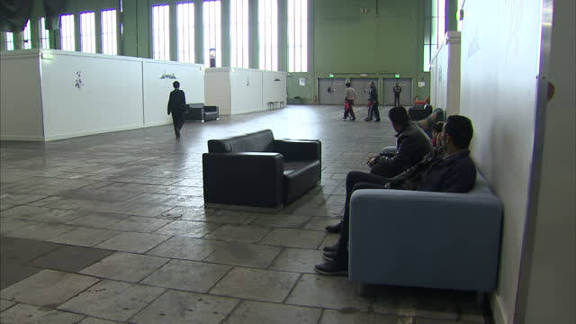 interior shots of refugees milling around in tempelhof airport hangar including families with young children on february 12 2016 in berlin germany - flüchtling stock-videos und b-roll-filmmaterial