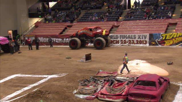vídeos de stock, filmes e b-roll de interior shots of remote control cars being driven around arena jumping off ramp and performing stunts remote controlled cars at monster truck rally... - controle