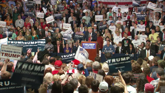 vídeos de stock e filmes b-roll de interior shots of republican candidate donald trump speaking at a campaign rally and crowds of supporters listening and cheering>> on march 07 2016... - comício político
