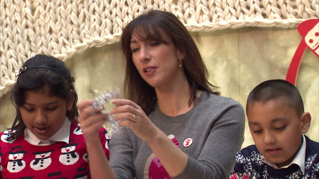 Interior shots of Samantha Cameron and Myleene Klass decorating Christmas jumpers with a group of children at an event promoting Save the Children's...