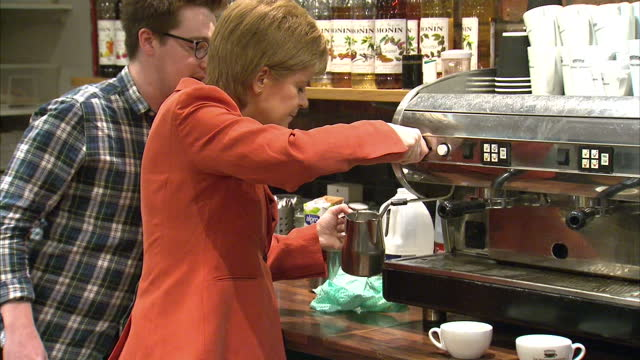 vídeos de stock, filmes e b-roll de interior shots of scottish national party leader nicola sturgeon trying her hand at making a cafe latte during a campaign visit on april 26, 2017 in... - stirling
