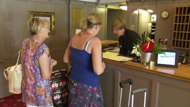 interior shots of several guests including a baby in a pushchair checking in to a worthing seaside hotel on 10 july 2015 in worthing, united kingdom - worthing点の映像素材/bロール