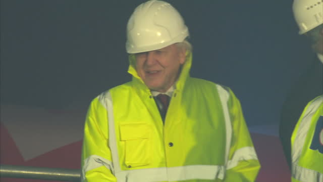 interior shots of sir david attenborough and other officials watching via screens as the first section of keel is moved into place to begin... - kiel rumpf stock-videos und b-roll-filmmaterial