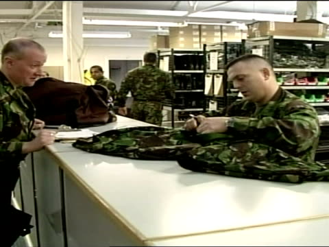 stockvideo's en b-roll-footage met interior shots of soldiers collecting army kit uniform from barracks ahead of iraq war tour of duty including shots of kit on shelves guns and... - helm apparatuur