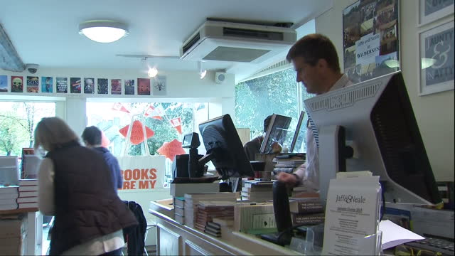 vídeos de stock e filmes b-roll de interior shots of staff serving customers and books on display in an independent bookshop>> on october 08 2015 in chipping norton united kingdom - chipping norton england