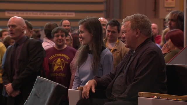 interior shots of star trek fans queueing for a photo opportunity with william shatner, and william shatner posing and speaking to fans while sitting... - william shatner stock videos & royalty-free footage