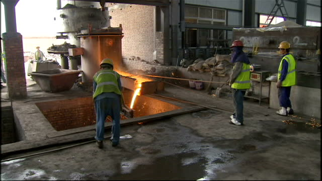 interior shots of steelworkers at work in steel plant with molten metal being poured from huge vats and into molds on july 7 2008 in beijing china - bottich stock-videos und b-roll-filmmaterial