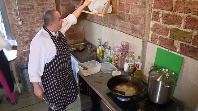 Interior shots of Syrian refugee Imad Alarnab cooking at his pop up restaurant in East London serving traditional food with the proceeds going...