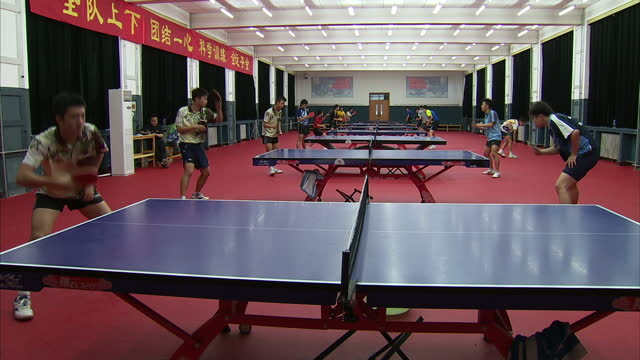 interior shots of table tennis sports people training in a hall with rows of tables and a poster in the school corridor xian hong sports technology... - sports poster stock videos & royalty-free footage