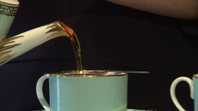interior shots of tea being poured through a strainer into a teacup and milk being added from a jug.>> on march 17, 2015 in london, england. - tea cup stock videos & royalty-free footage