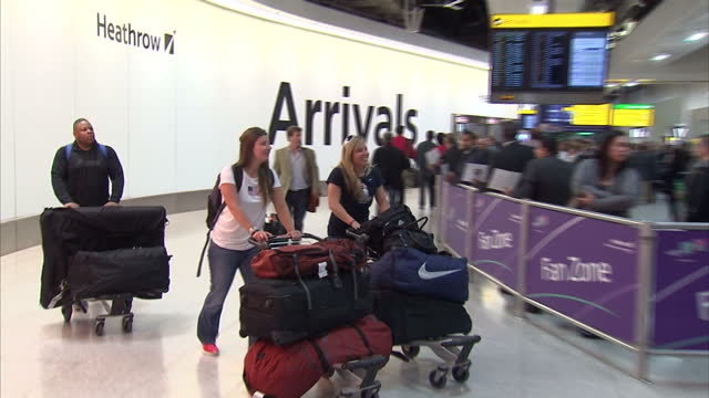 interior shots of team usa olympic team walk with suitcases on arrival at heathrow airport sky news 2012 olympics coverage at heathrow airport on... - united states national team stock videos & royalty-free footage