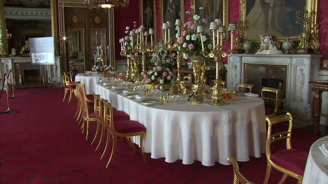 interior shots of the ballroom of buckingham palace with tables set in replica of the settings used for the coronation banquets exhibition of the... - バッキンガム宮殿点の映像素材/bロール