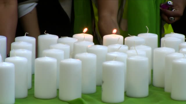 interior shots of the congregation lighting candles in tribute to the victims who lost their lives during the grenfell tower fire at the memorial... - トリビュート・イベント点の映像素材/bロール